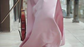 Den oigenkännliga violinisten, i att blåsa klänningen och fiolen i hand, går på kamera lager videofilmer