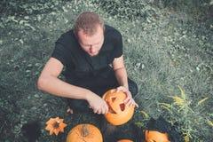 Den oigenkännliga mannen klipper en pumpa, som han förbereder stålar-nolla-lyktan halloween Garnering för parti tonat foto Royaltyfria Foton