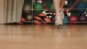 Den okända kvinnan hoppar over med hopprepet på den moderna idrottshallen Ingen framsida 4K arkivfilmer