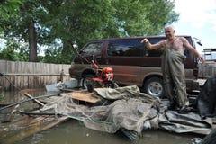 Den okända mannen sparar en bil under en flod på de skapade högländerna Royaltyfri Foto