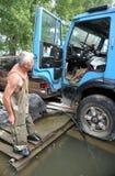 Den okända mannen sparar en bil under en flod på de skapade högländerna Arkivbilder