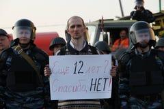 Den okända personen som protesterar med en affisch i bakgrunden av polisen för aktierna av rysk opposition för ganska val, kan 6, Arkivfoto