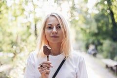 Den okonventionella nätta flickan äter glass Arkivbilder
