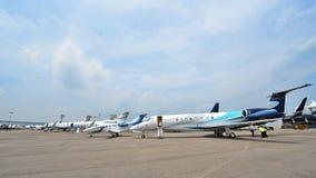 Den olika Embraer och Gulfstream ledaren sprutar ut på skärm på Singapore Airshow Arkivfoton