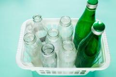Den olika glasflaskan slöser bort klart för återanvändning i den vita korgen på grön bakgrund Socialt ansvar, ekologiomsorg, royaltyfri fotografi