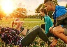 Den olika gruppen av millenials under konditiongrupp som gör sitta-UPS på solnedgången i natur, parkerar arkivfoto