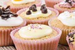 Den olika muffinen på ett trä bordlägger Fotografering för Bildbyråer