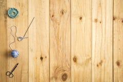 Den olika sömnaden bearbetar, inklusive sax, ulltrådar och visare på ljus wood bakgrund Royaltyfria Foton