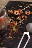 Den olika sorten av den organiska torkade örter, frukt och blomman dekorerade med teinfuser på svart bakgrund Royaltyfri Fotografi