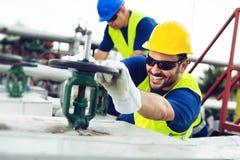 Den olje- arbetaren stänger ventilen på den olje- rörledningen royaltyfria bilder