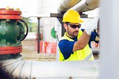Den olje- arbetaren stänger ventilen på den olje- rörledningen arkivfoton