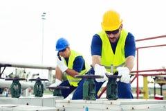 Den olje- arbetaren stänger ventilen på den olje- rörledningen royaltyfri bild