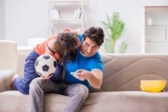 Den olyckliga frun som maken håller ögonen på fotboll royaltyfria bilder