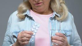 Den olyckliga gamla kvinnan som rymmer piller och vattenexponeringsglas suckar SAD, trött av behandling lager videofilmer