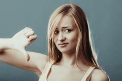 Den olyckliga kvinnan som ger tummen gör en gest ner Royaltyfri Fotografi
