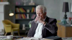 Den olyckliga ledsna och besvärade äldre mannen ser incredulously en preventivpiller och tar den stock video