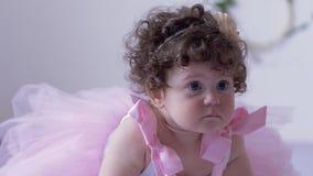 Den olyckliga lilla flickan med lockigt hår i rosa färger klär närbilden som poserar i den vita studion stock video