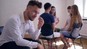 Den olyckliga mannen tänker om problem på gruppterapiperiod på bakgrund av folk som sitter på stolar i en cirkel lager videofilmer