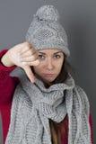 Den olyckliga vinterflickan som uttrycker besvikelse med tummen ner och, trutar Royaltyfria Foton