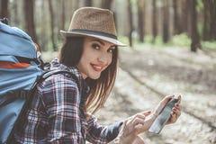 Den optimistiska flickan är den hållande smartphonen arkivbild