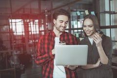 Den optimistiska mannen och kvinnan tycker om espresso på arbete royaltyfria foton