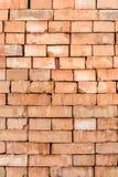 Den orange bakgrunden av den texturerade tegelstenen läggas ner kullarna Fotografering för Bildbyråer