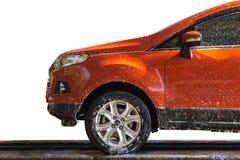 Den orange bilen med vit tvål på kroppen i bilomsorg shoppar arkivfoto