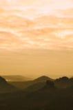 Den orange dimmiga morgonen sikt över vaggar till den djupa dalen mycket av det drömlika vårlandskapet för ljus mist inom gryning Royaltyfri Bild