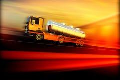 Den orange halva lastbilen med den olje- cisternen på hastighet blured asfaltvägen Royaltyfri Bild