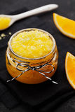 Den orange kroppen skurar med socker- och kokosnötolja i den glass kruset på tappningbakgrund Hemlagad skönhetsmedel för skalning royaltyfri foto