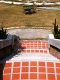 Den orange kvartertrappan går till den gröna rottingstolen Royaltyfria Bilder