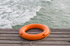 Den orange livbojet som är pålagd porten nära havet Arkivbilder