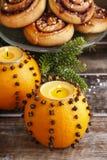 Den orange pomanderen klumpa ihop sig med stearinljus och kanelbruna rullar Royaltyfri Bild