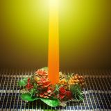 Den orange stearinljuset på tabellen med julgarnering Arkivbilder