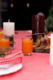Den orange stearinljuset står på tabellen Festlig sammansättning med stearinljus undersöker inpackning för julgarneringtabell En  Arkivfoton