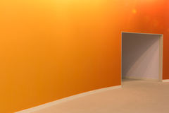 Den orange väggen och öppnar ingången i ett tomt rum Arkivfoto