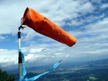 Den orange windsocken (weathervane) överst av berget Arkivfoto