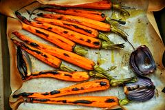 Den organiska nya morötter och löken grillade i ugnen Royaltyfri Bild