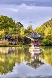 Den orientaliska paviljongen reflekterade i vatten på solnedgången, Lijiang, Kina Arkivbild