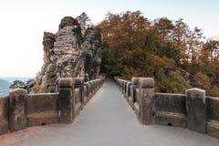Den orienterade sikten på den Bastei bron med träd och vaggar i höstlynne royaltyfria foton