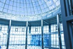 Den original- designen av exponeringsglas och metall i form av en kupol av en skyskrapa, blå himmel Arkivbilder