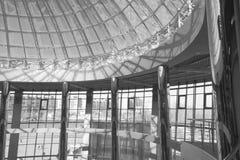 Den original- designen av exponeringsglas och metall i form av en kupol av en skyskrapa, blå himmel Arkivbild