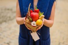 Den original- ovanliga ätliga grönsak- och fruktbuketten i flickahänder Fotografering för Bildbyråer