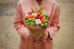 Den original- ovanliga ätliga grönsak- och fruktbuketten i kvinnahänder Royaltyfri Fotografi