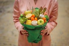 Den original- ovanliga ätliga grönsak- och fruktbuketten i kvinnahänder Arkivfoton