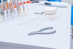 Den OrthodontistDental uppsättningen av klämmor och plattång och andra hjälpmedel på den funktionsdugliga tabellen ytbehandlar Royaltyfri Bild