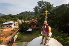Den ortodoxa prästen förnyar kors på kupoler av kyrkan Arkivbilder
