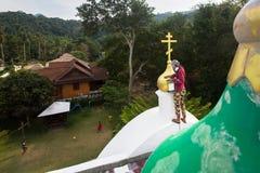 Den ortodoxa prästen förnyar kors på kupoler av kyrkan Royaltyfria Bilder