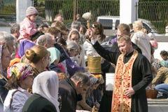 Den ortodoxa prästen stänker det heliga vattnet på påskkakor royaltyfri foto