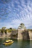 Den Osaka slotten och ett turist- fartyg i staden omger med vallgrav Arkivbild